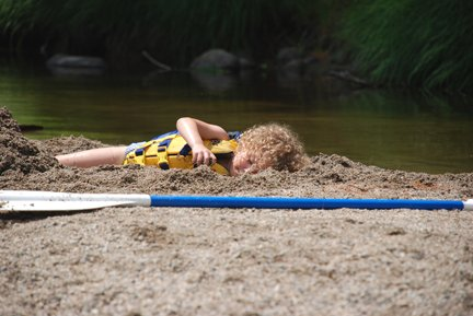 Child laying in sand after whitewater rafting trip