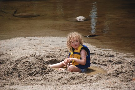 Child plaing in the sand after whitewater rafting trip