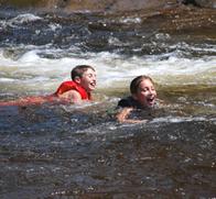 children swimming at bottom of water slide